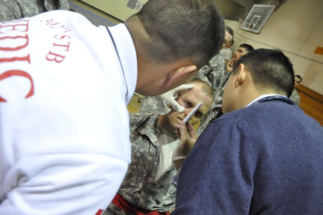 Michael Rowley, Headquarters and Headquarters Company, Special Troops Battalion-Korea, is examined by the 501st Special Troops Battalion medical team following a controversial knee to the face.  Rowley finished 2nd in cruiserweight division of the Area IV Better Opportunities for Single and Unaccompanied Soldiers  Combatives Tournament at Camp Carroll, South Korea Apr. 16.