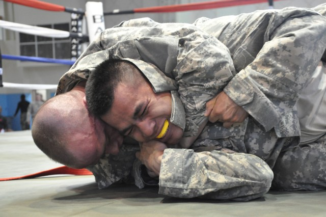 Joe Clark (left), 2nd Infantry Division,  chokes Vinh Oh, 602nd Aviation Support Battalion (right), during the Area IV Better Opportunities for Single and Unaccompanied Soldiers  Combatives Tournament at Camp Carroll, South Korea Apr. 16.