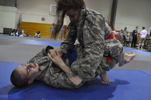 Sabrina Martinez (top), Headquarters and Headquarters Company, Special Troops Battalion-Korea, pummels with Robert Llewelly (bottom), 168th Multifunctional Medical Battalion, during the Area IV Better Opportunities for Single and Unaccompanied Soldiers  Combatives Tournament at Camp Carroll, South Korea Apr. 16.