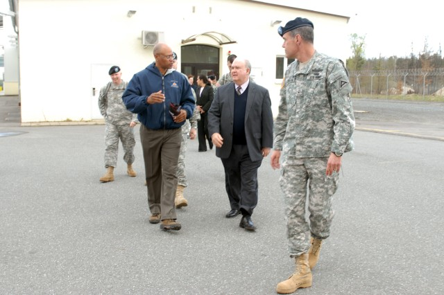 GRAFENWOEHR, Germany - Joseph W. Westphal, under secretary of the United States Army, listens to Allen D. Drew (left), site lead and contractor, CSC, as Brig. Gen. Steven L. Salazar, (right), commanding general of the 7th Army Joint Multinational Training Command, escorts Westphal and his staff to the Multi-cultural Mobile Counter Improvised Explosive Device Interactive Trainer (McMCIT) trailers here in Motorpark 7, April 12, 2011. The McMCIT, a cognitive training system and only one in the world, is designed to teach Soldiers to identify visual indicators of an IED, react to a suspected IED, and perform the necessary reporting after an IED incident in four languages: English, Polish, Bulgarian, and Romanian. The training system was developed as part of U.S. Secretary of Defense Robert M. Gates directive to support partnered nations to increase the effectiveness of Counter-IEDs, and funded by the Joint Improvised Device Defeat Organization (JIEDDO) for use by U.S and multinational forces.