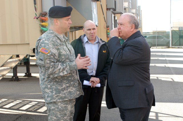GRAFENWOEHR, Germany - Joseph W. Westphal, under secretary of the United States Army, listens to Maj. James Hickman (left), deputy of Training Support Activity-Europe, gives a brief overview of the Multi-cultural Mobile Counter Improvised Explosive Device Interactive Trainer (McMCIT) here April 12, as Daniel W. Feazelle (center), chief, Regional Training Support Center - Grafenwoehr, observes. The McMCIT, a mobile system for CIED training - and the only one in the U.S. Army specifically designed for use by multinational partners, is designed to teach Soldiers to identify visual indicators of an IED, react to a suspected IED, and perform the necessary reporting after an IED incident in four languages: English, Polish, Bulgarian, and Romania. The training system was developed as part of U.S. Secretary of Defense Robert M. Gates directive to support partnered nations to increase the effectiveness of Counter-IEDs, and funded by the Joint Improvised Device Defeat Organization (JIEDDO) for use by U.S and multinational forces.