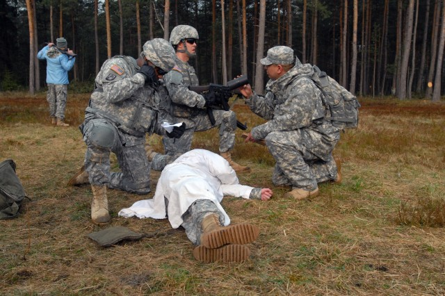 GRAFENWOEHR, Germany - A Soldier attending the Warrior Leader Course, class 07-11 from Bravo Company, 7th Army Noncommissioned Officer Academy, radios in a simulated 9-line MEDEVAC (medical evacuation) request to his higher headquarters here, April 11, while questioned and filmed by an embedded media reporter. The WLC is the initial leadership course for U.S. Army enlisted Soldiers where they are trained in various garrison and tactical leadership lessons while enhancing their leadership potentials. Under the auspice of the Joint Multinational Training Command, the 7th Army NCOA is the first and oldest NCOA in the U.S. Army, and works to build partnership capacity by incorporating relevant training to the contemporary operating environment. The JMTC is the only place in the U.S. Army that regularly trains with multinational partners.
