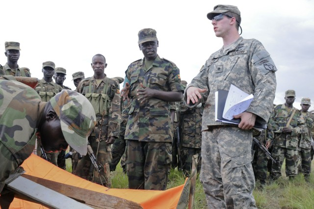 Spc. Dustin Terry of Hiram, Ga., who serves as a pathfinder with Troop C, 3rd Squadron, 108th Cavalry Regiment, Georgia National Guard, instructs Soldiers from the 27th Infantry Battalion, Uganda People's Defense Forces, on how to set up drop zone marking panels at DZ Red near Kapelebyong, Uganda, during Atlas Drop 11, April 14.