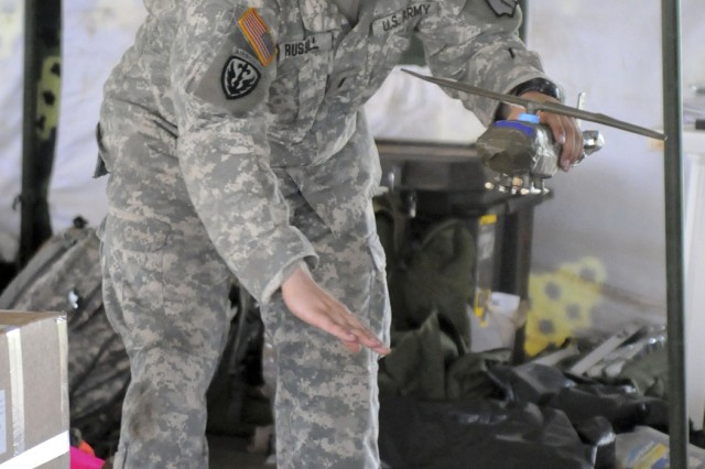 1st Lt. Steven Russell of Dahlonega, Ga., a member of Troop A, 3rd Squadron, 108th Cavalry, who serves as the pathfinder team leader and lead instructor for one of the drop zone training teams, uses a model helicopter made from duct tape and a water bottle to illustrate a cargo drop during training at DZ Red near Kapelebyong, Uganda, during Atlas Drop 11, April 14.