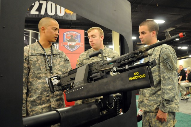 Spc. Jose Palomino, Spc. James Cobb, and Spc. Kenneth Waller, look at a modified M240 machine  gun that is mounted in a mock-up door frame from a CH-47 Chinook helicopter during the 2011 Army Aviation Association of America's Annual Professional Forum and Exposition in Tennessee.  The M240's turret mount has been modified to ensure the weapon doesn't hit the window frame.