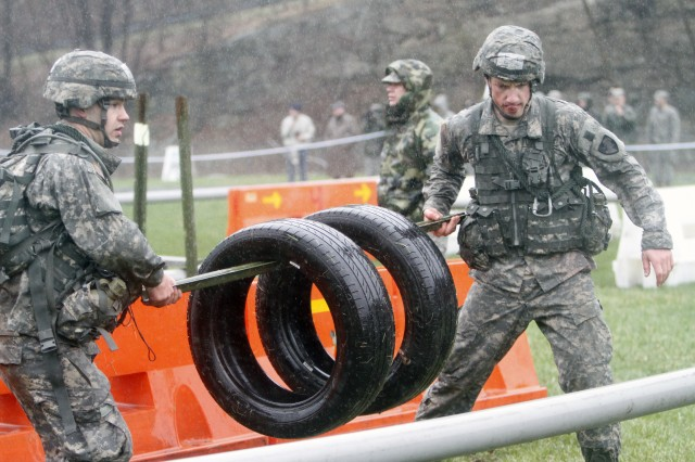 Company E-1 Cadets carry tires through an obstacle course on their way to the finish line. The DMI Challenge was the final test before completing the 45th annual Sandhurst Military Skills Competition April 15-16, 2011, at Camp Buckner, at West Point, N.Y. The event required teams to heavy carry tires, ammo containers and other equipment through a series of obstacles. Only cadets wearing the designated color could touch certain objects, so failure to negotiate the course or touching an unauthorized object resulted in penalties.