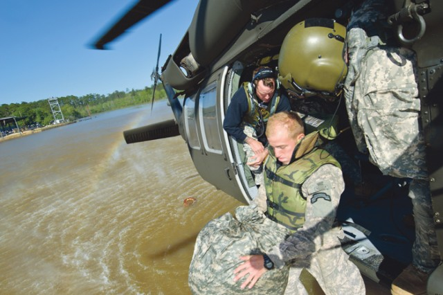 Teams jump Sunday from a Black Hawk helicopter into Victory Pond at Fort Benning, Ga., during the helocast event. The teams must wrap their gear with a waterproof liner. If done correctly, they can swim it to shore without any items getting wet.