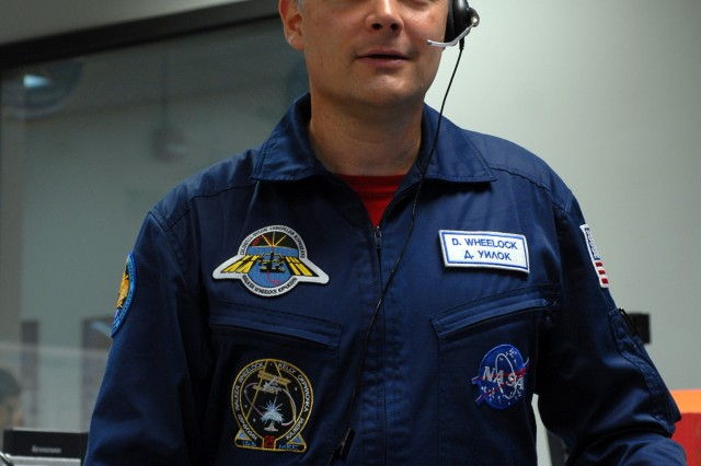 Col. Doug Wheelock, wearing a blue Russian space suit, is the first active-duty Army astronaut to command the International Space Station. He visited Marshall Space Flight Center on April 11 to express his gratitude for the support the Expedition 25 crew received from employees of the Payload Operations Center. During a visit to the Payload Operations Center, he wears a headset to talk to the International Space Station crew.