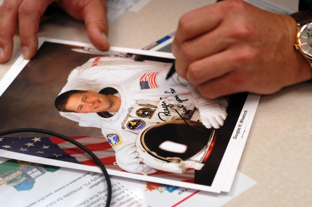 Col. Doug Wheelock autographs a photograph for a Marshall Space Flight Center employee.
