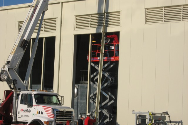 On the Utility Building exterior, workers safely install louvers to shield the interior boilers from the elements. Once complete, the Utility Building will house equipment to produce steam, compressed air, chilled water and hot water for operations.
