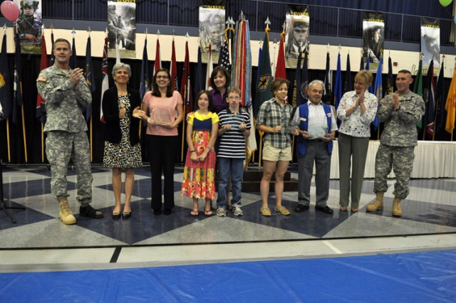 Maj. Gen. James and Kim Milano, and Command Sgt. Maj. Brian and Cheryl Stall recognize Volunteers of the Year during a ceremony Friday.