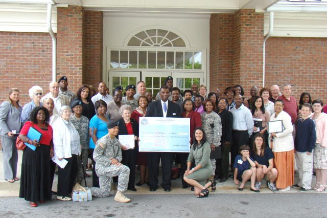 Volunteers pose together with Howard Butler (center holding check), U.S. Army Garrison deputy commander, outside The Commons at Fort McPherson following the Installation Volunteer Recognition Ceremony April 14. The 392 volunteers honored at the ceremony contributed $489,586.82 worth of man-hours toward improving the community, according to the Army Volunteer Corps advisory council.