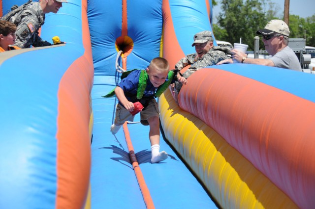Wyatt Barrs, military child, fights against the tug of a large rubber band as he tries to place a beanbag in the goal of one of the inflatable games during the annual Children's Festival at the festival fields  Saturday.