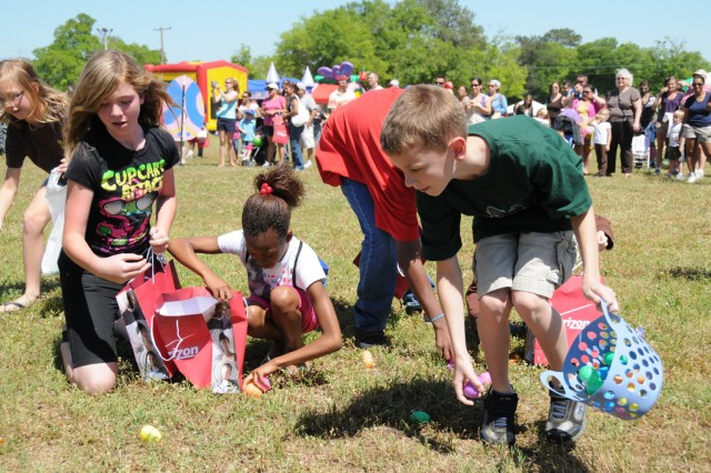 A group of military children grab up as many eggs as they can during the Easter egg hunt portion of the annual Children's Festival at the festival fields Saturday. Each egg contained either candy or a prize ticket.