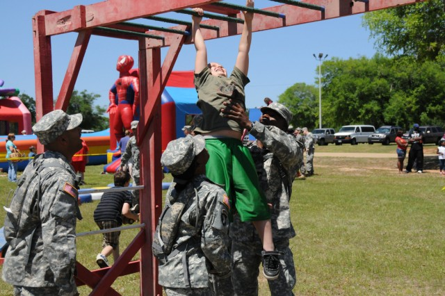 Corbin Grey, military child, gets some help from a group of Warrant Officer Candidates as he runs an obstacle course during the annual Children's Festival at the festival fields Saturday.