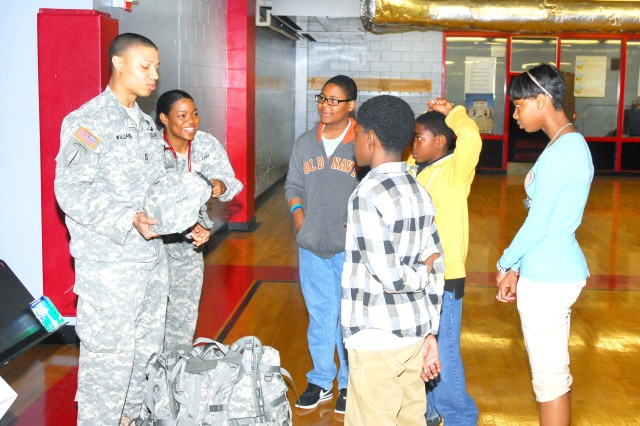 Williams and Natalie talk with some students about the protective gear they wear as Soldiers.