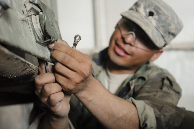 CONTINGENCY OPERATING BASE ADDER, Iraq - Spc. Luis Reyes, a wheeled vehicle mechanic from Dallas with B Field Maintenance Company, 215th Brigade Support Battalion, 3rd Advise and Assist Brigade, 1st Cavalry Division, removes the plate from an interface cable port on a trailer. Reyes and the other mechanics he works with keep their skills tuned and motivation high by relying on each other for mechanical advice and camaraderie.