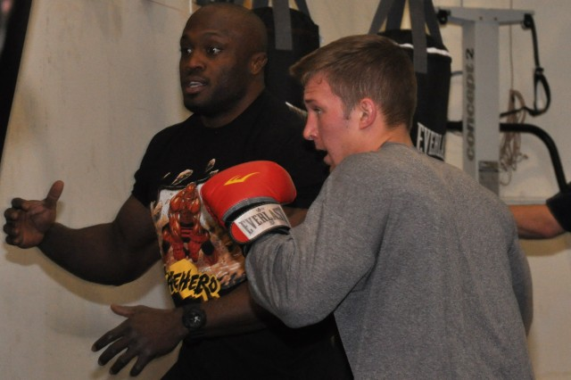 Professional mixed martial arts fighter Bobby Lashley, left, instructs Sgt. Erik Slott on proper technique while using the heavy weight bag during drills April 15. Slott is a the U.S. Army Space and Missile Defense Command/Army Forces Strategic Command.