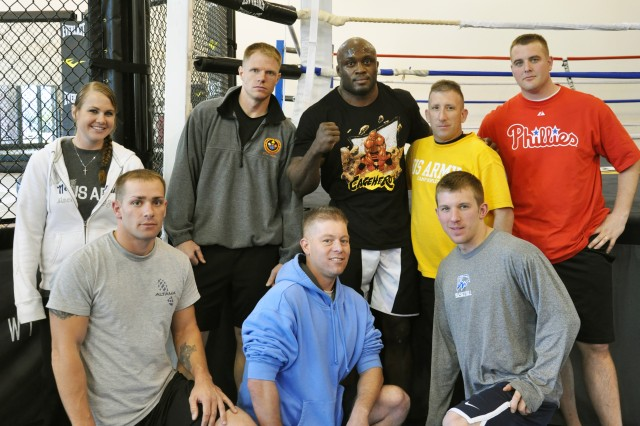Soldiers from Headquarters and Headquarters Company and the 53rd Signal Battalion pose for a photo after a training session with Bobby Lashley on April 15.