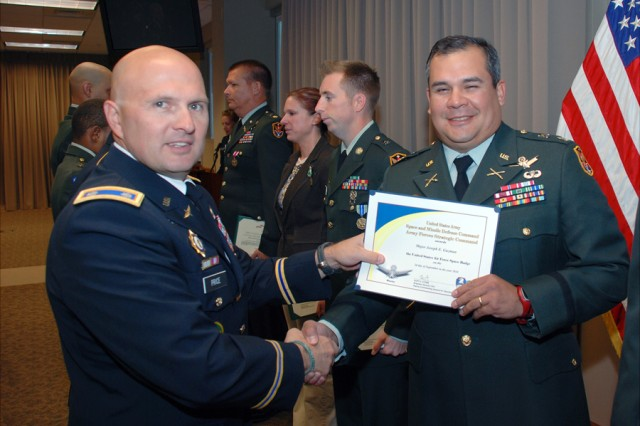 Lt. Col. John D. Price, 1st Space Battalion commander, presents the Master Space Badge to then Maj. Joseph E. Guzman, 1st Space Brigade, during a monthly awards ceremony at Peterson Air Force Base, Colo., in October. Guzman has since been promoted to lieutenant colonel.