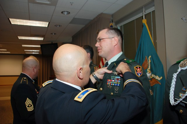 Lt. Col. John D. Price, 1st Space Battalion commander, pins the Basic Space Badge on Sgt. 1st Class Erik A. Johnson, 4th Space Company, 1st Space Battalion, during a monthly awards ceremony at Peterson Air Force Base, Colo., in October.