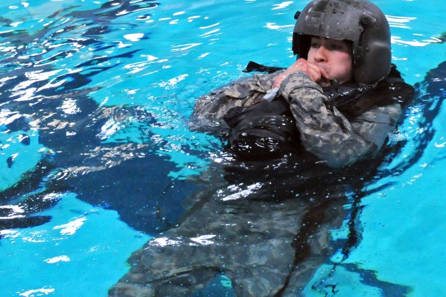 Spc. David Pliego inflates his low profile floatation device during the floatation portion of the flight crew training at JBLM. The training is an annual requirement for crew members to maintain their aviation water survival certification.