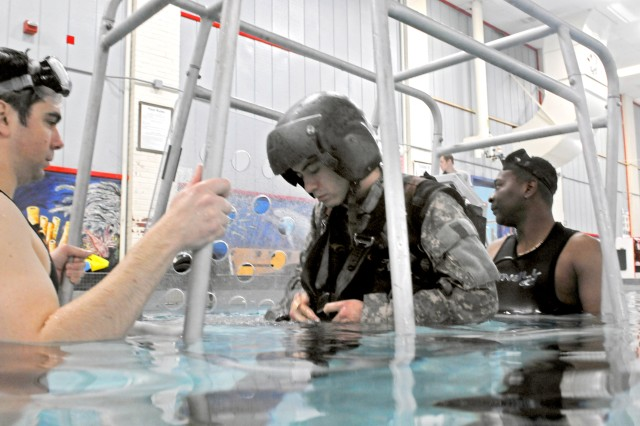 Spc. David Pliego straps in for his final ride in the shallow water egress trainer while Spc. Adam Kesmetis, Aviation Life Support Equipment  rescue swimmer, looks on.