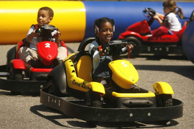 Damian Jung, 3, Nevaeh Thomas, 5, and Allison Loveland, 3, test out the miniature electric cars at Burba Park. The Earth Day festivities had fun events for all ages.