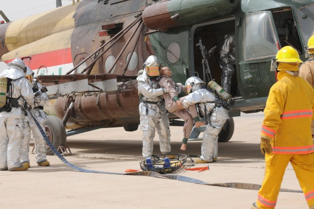 Firefighters from Sather Air Force Base Fire Department pull an injured pilot from a helicopter. The firefighters participated in a simulated aircraft egress exercise as a demonstration for Iraqi firefighters to observe on Sather Air Force Base, April 18.