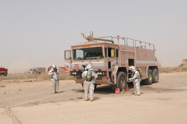 Firefighters from Sather Air Force Base Fire Department positioned a fire truck in a safe zone before approaching a distressed helicopter. The firefighters participated in a simulated aircraft egress exercise as a demonstration for Iraqi firefighters to observe on Sather Air Force Base, April 18.
