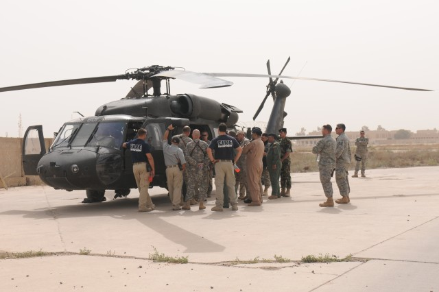 U.S. and Iraqi firefighters, crew members and translators gathered around a black hawk helicopter during an aircraft familiarization and egress exercise on Sather Air Force Base, April 18.
