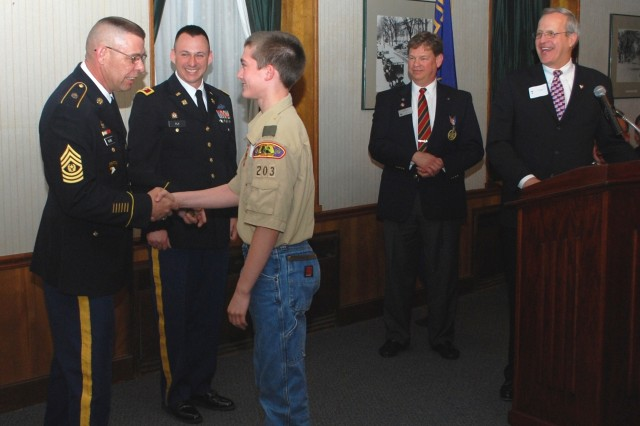 ASC's Command Sgt. Maj. Stephen D. Blake congratulates Cody James of Troop 203 at the 2011 Illowa Council Eagle Scout recognition dinner. Col. James Fly, second from left, commander of the RIA Joint Manufacturing and Technology Center and Boy Scout council members assist.