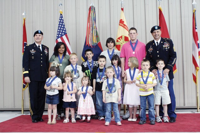 Children of fallen servicemembers pose for a photo with Brig. Gen. Randal Dragon, 1st Infantry Division deputy commanding general, (far left) and 1st Inf. Div. Command Sgt. Maj. Jim Champagne, (back row right) following the Ceremony of Remembrance April 10, 2011, at Marshall Army Airfield on Fort Riley, Kan.