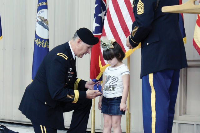 Brig. Gen. Randal Dragon, 1st Infantry Division deputy commanding general, (left) awards Jennifer Knopp, daughter of Sgt. Ralph Mena, with a gold medal of remembrance April 10, 2011, during Fort Riley's Ceremony of Remembrance, as 1st Inf. Div. Command Sgt. Maj. Jim Champagne, (right) looks on, at Marshall Army Airfield on Fort Riley, Kan.