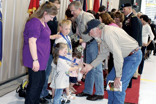 Retired Maj. Drew Dix, Vietnam War veteran and Medal of Honor recipient, shakes hands with Kaleigh Bachman, daughter of fallen Soldier Sgt. 1st Class Travis Bachman, following the Ceremony of Remembrance April 10, 2011, at Marshall Army Airfield at Fort Riley, Kan.
