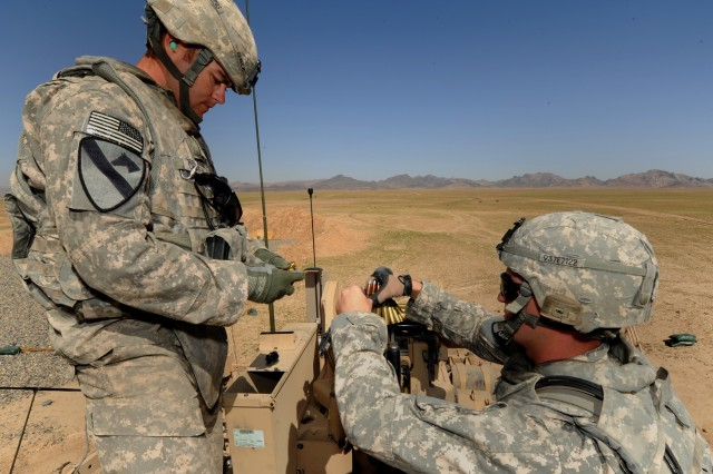 KANDAHAR PROVINCE, Afghanistan - U.S. Army Staff Sgt. Aaron Craven, squad leader (left), and Pfc. Jerik Erskine, a gunner, both assigned to 1st Platoon, 937th Route Clearance Company, 8th Engineer Battalion, 36th Engineer Brigade, deployed from Fort Hood, Texas, load ammunition into an M2 .50-caliber machine gun on top of an RG-31 Mine Resistance Ambush Protected vehicle before weapons familiarization training outside of Forward Operating Base Jelawur, Kandahar province, Afghanistan, April 20, 2011. (U.S. Air Force photo/ Staff Sgt. Stephen D. Schester, 16th Mobile Public Affairs Detachment)