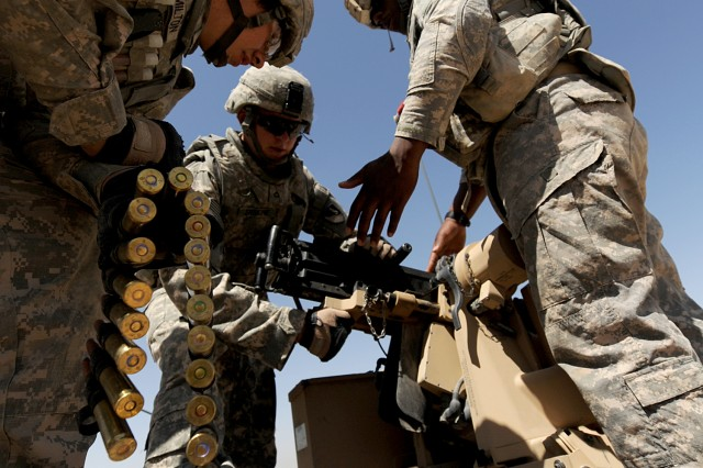 KANDAHAR PROVINCE, Afghanistan-U.S. Army Pfc. Dustin Hamilton (left), Pfc. Jerik Erskine (middle) and Pfc. Marcel Duncan (right), all assigned to 1st Platoon, 937th Route Clearance Company, 8th Engineer Battalion, 36th Engineer Brigade, deployed from Fort Hood, Texas, load ammo into a M-2 .50-caliber machine gun on top of an RG-31 Mine Resistance Ambush Protected vehicle before weapons familiarization training outside of Forward Operating Base Jelawur, Kandahar province, Afghanistan, April 20, 2011. (U.S. Air Force photo by Staff Sgt. Stephen D. Schester, 16th Mobile Public Affairs Detachment)