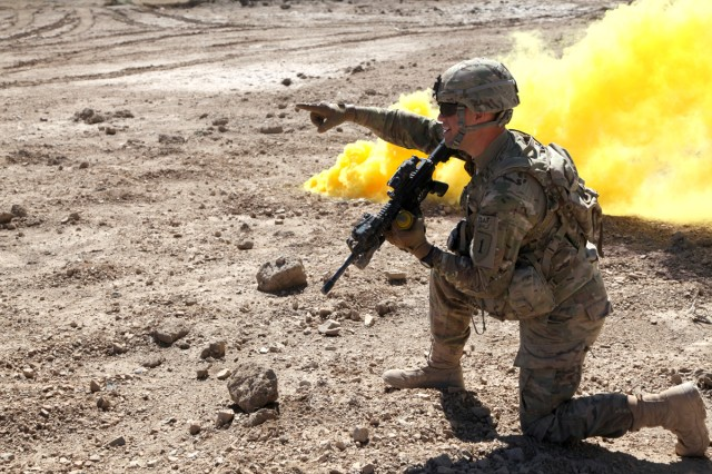 U.S. Army Soldier Pfc. Brad Palmer from Billings, Missouri, with 3rd Platoon Bravo Company, 1st Battalion 26th Infantry Regiment, 3rd Brigade 1st Infantry Division, out of Fort Knox, Ky, marks the drop zone with yellow smoke, outside of Combat Outpost Sabari, Khowst province, Afghanistan, Mar. 09, 2011 (U.S. Army photo by PFC. Donald Watkins/Released)