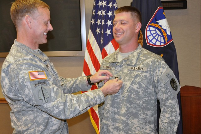 USASMDC/ARSTRAT Deputy Commanding Officer for Operations Col. Timothy Coffin replaces the lieutenant rank on Harold Butterfield's uniform with captain's bars. Butterfield was promoted during a ceremony on April 15 at Peterson Air Force Base, Colo. Butterfield serves as Coffin's aide.