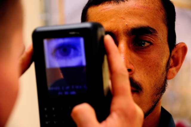 Spc. Brady Klock, a supply technician from Charlie Battery, 2nd Battalion, 44th Air Defense Artillery Regiment, based at Fort Campbell, Ky., scans the eye of an Afghan National Civil Order Police trainee as he puts the trainee's information into the biometrics system at the Police Regional Training Center Mehtar Lam, Afghanistan, April 18, 2011.