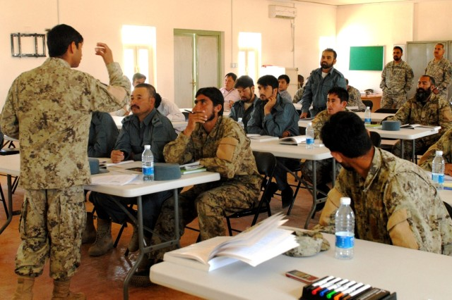 An Afghan National Civil Order Police instructor discusses techniques during the Afghan National Police-led Combat Medic Course April 23 at the Joint Regional Afghan National Police Center, Kandahar province, Afghanistan. Course instructors are graduates of the Afghan National Army-led combat medic course at the Regional Military Training Center nearby. This class also includes linguists (in civilian clothes).