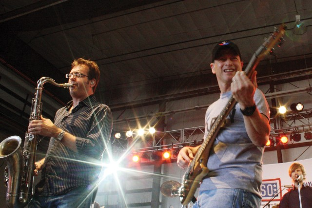 Mitch Paliga, on saxophone, and Gary Sinise, on bass, perform during a song at the Gary Sinise and the Lt. Dan Band concert April 10, 2011, as the finale to the Month of the Military Child festival at Marshall Army Airfield, Fort Riley, Kan.