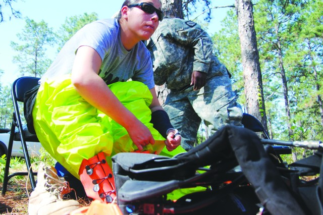 Pfc. Maria Chatfield, 83rd Chemical Battalion, dons a protective suit before going on a recon mission during a training exercise April 13 at Fort Polk's Rosepine 2 training area. Chatfield is a member of the 83rd Chem Bn's hazardous response