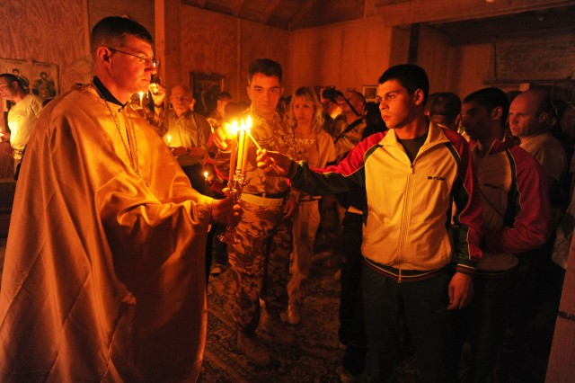 KANDAHAR AIRFIELD, Afghanistan --  Chaplain (Capt.) Sean Levine, 117th Infantry Battalion, 2nd Stryker Brigade Combat Team, presents the trikeri or triple candle, which represents the Holy Trinity, for the observers to light candles during an Eastern Orthodox Easter or Pascha (a Christian version of Passover) service at Kandahar Airfield, Afghanistan, April 23, 2011. (U.S. Army photo by Sgt. Jennifer Spradlin, 16th Mobile Public Affairs Detachment)