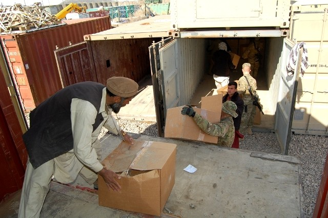 Spc. David Gordy, a member of 1st Battalion, 168th Infantry Regiment, 2nd Brigade, 34th Infantry Division, Task Force Lethal, helps a worker from Gardez City, Paktya province, unload a truckload of more than 400 boxes full of coats, hats, gloves and scarves on Forward Operating Base Gardez, Afghanistan, March 7, 2011. Rapport Afghanistan, a U.S. volunteer group that provides comfort supplies to the rural areas of Afghanistan, donated the goods. TF Lethal and their Government of Islamic Republic of Afghanistan partners later distributed the winter clothing to local Afghans throughout Paktya province.