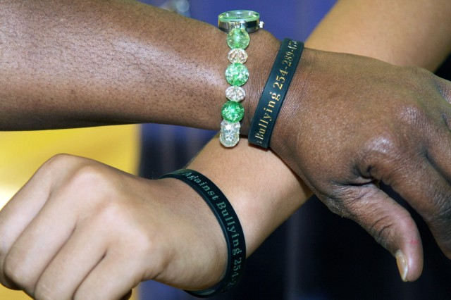 """Seventh-grade students show their """"Bully Bands,"""" which provide students with a phone number they can call or text to report an incident of bullying."""