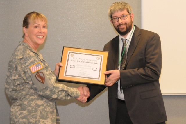 "Mr. Jeffrey ""Thom"" Hawkins (right), program analyst for Program Executive Office Command, Control, Communications-Tactical (PEO C3T) Business Management Division, Program Analysis Branch, received his Black Belt Certification Certificate from Brig. Gen. N. Lee S. Price, PEO for C3T, for his Lean Six Sigma Efforts."