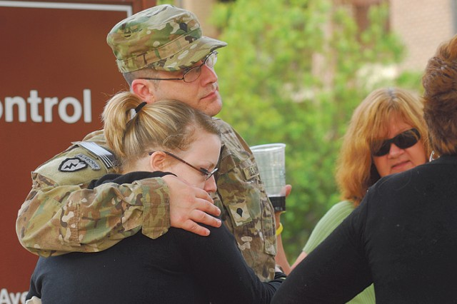 Spc. Scott Taylor comforts his wife, Jessie, and two children as the family prepares for his second deployment. The unit is headed to Kandahar, Afghanistan.