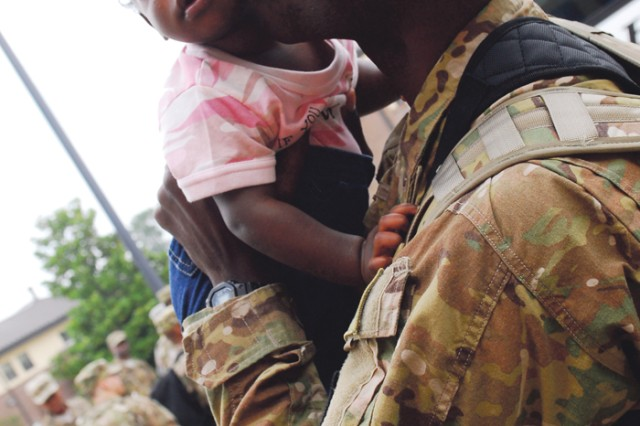 Ten-month-old Taylor gets a kiss Wednesday from her father, Capt. Travis Tribble, shortly before he boards a bus bound for Atlanta.