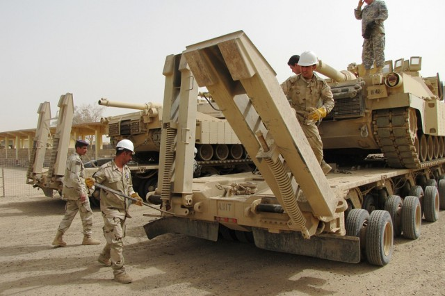 """Sgt. 1st Class Alan Moore, (right) with Headquarters and Headquarters Company, 299th """"Lifeline"""" Brigade Support Battalion, 2nd Advise and Assist Brigade, 1st Infantry Division, United States Division - Center, instructs soldiers with the 9th Iraqi Army on the loading procedures of an M1A2 Main Battle Tank onto a Heavy Equipment Transport Trailer during training at Camp, Taji, Iraq, April 17, 2011. The training was part of a nine-day """"train-the-trainer"""" course intended to leave an enduring capability for transporting heavy equipment with the Iraqi Army."""
